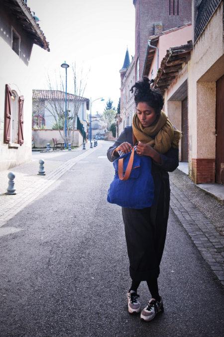 dans les rues de l'isle jourdain, une fille pose avec un cabas bleu en lin