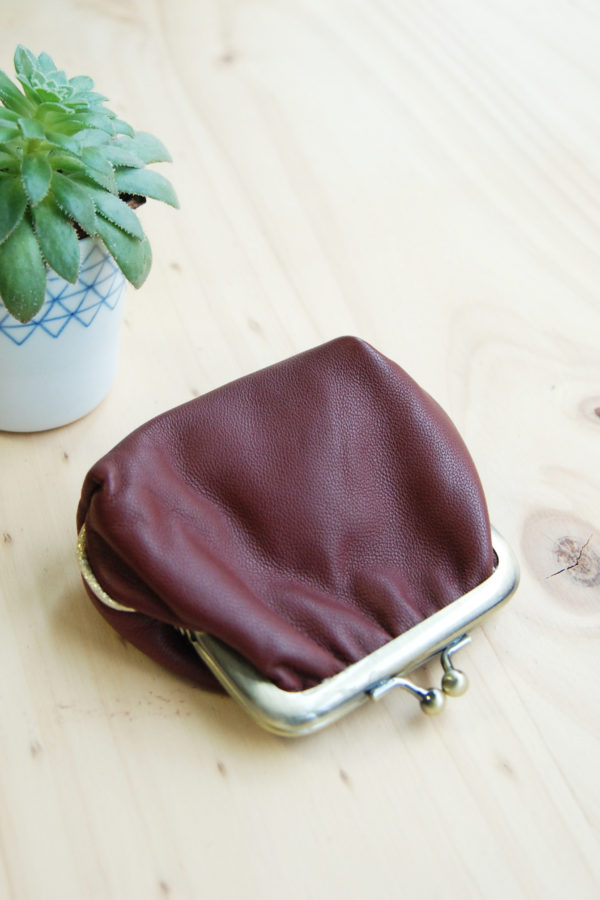 porte-monnaie rétro en cuir avec fermoirs laiton exposé sur une table