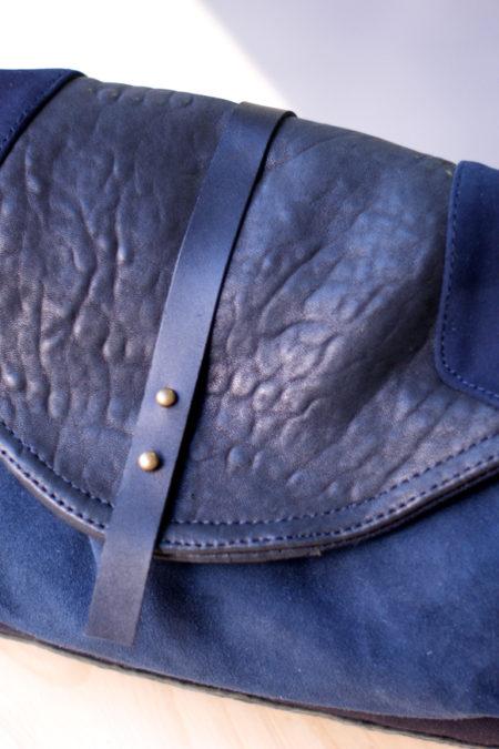 sac besace en cuir et toile bleue posée sur une chaise