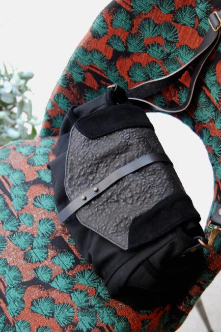 un sac en cuir noir et toile de coton noire est posée sur une chaise retapissée