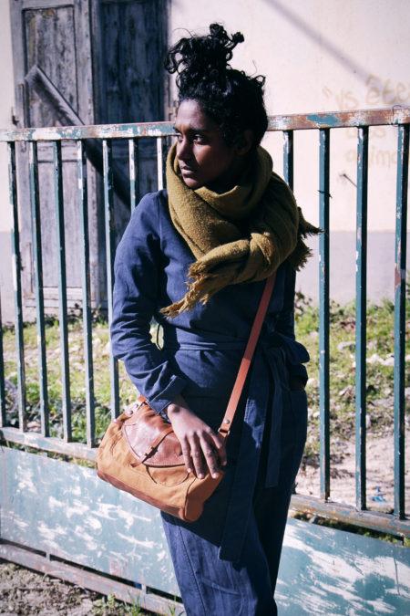 une fille porte devant une batisse abandonnée un sa en cuir et coton , une pièce unique.