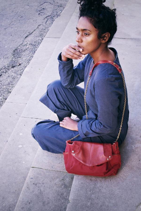 une fille posée sur des marches avec son sac rouge en bandoulière