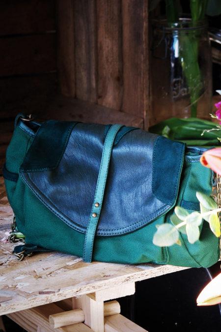 sac vert sapin en cuir et toile de coton posé sur la table d'une fleuriste