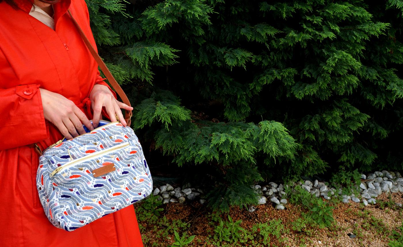 sac créateur en tissu jacquard bleu porté par un modèle au trench rouge