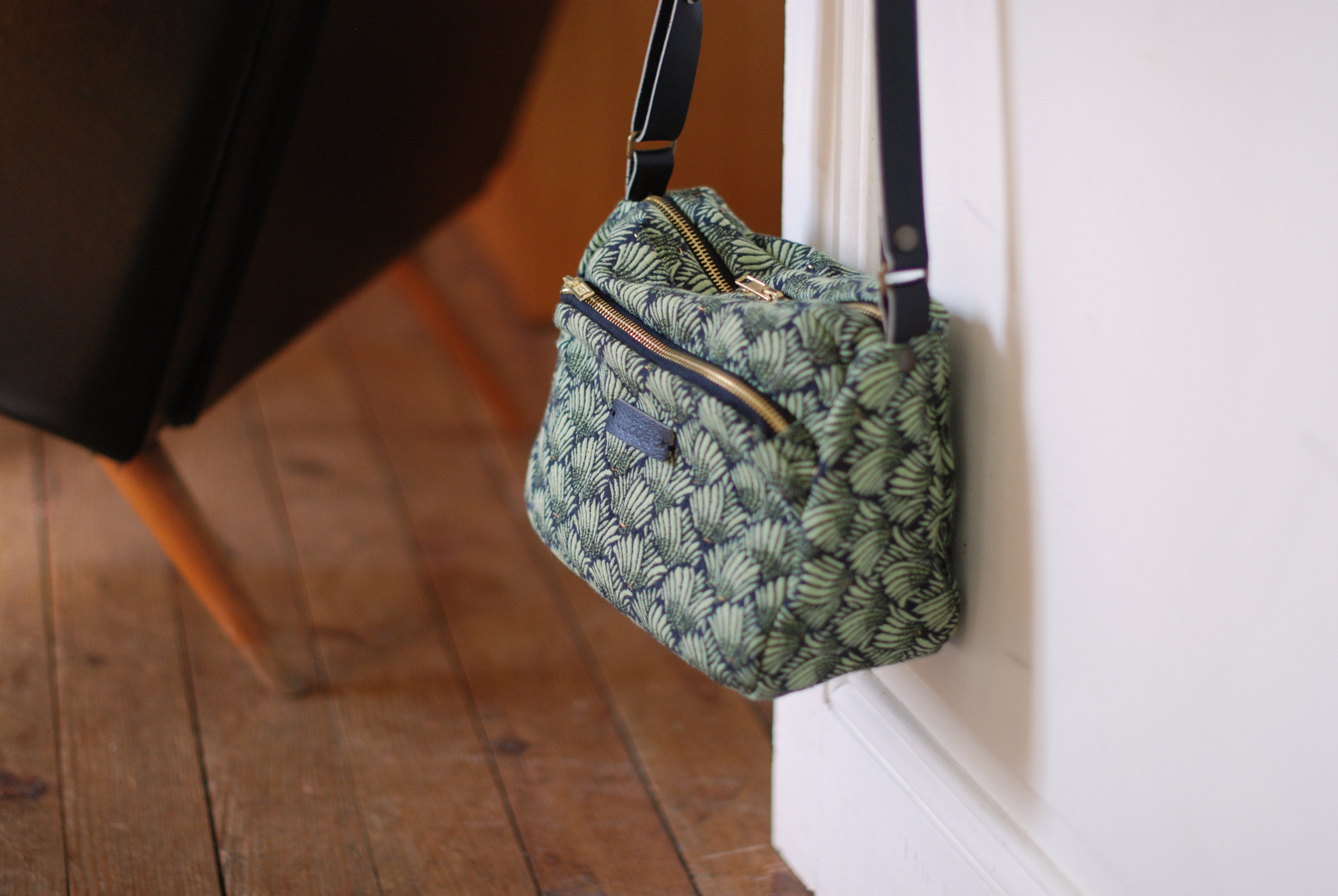 un sac à motifs vert et noir est suspendu à la poignée d'une porte